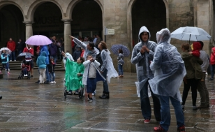 Peregrinos e turistas baixo a chuvia, esta semana, en Santiago - FOTO: Fernando Blanco