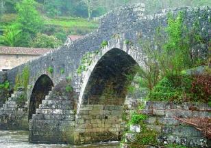 Estado actual del viaducto de A Ponte Maceira, con maleza y grietas en el arco.  - FOTO: M.M.