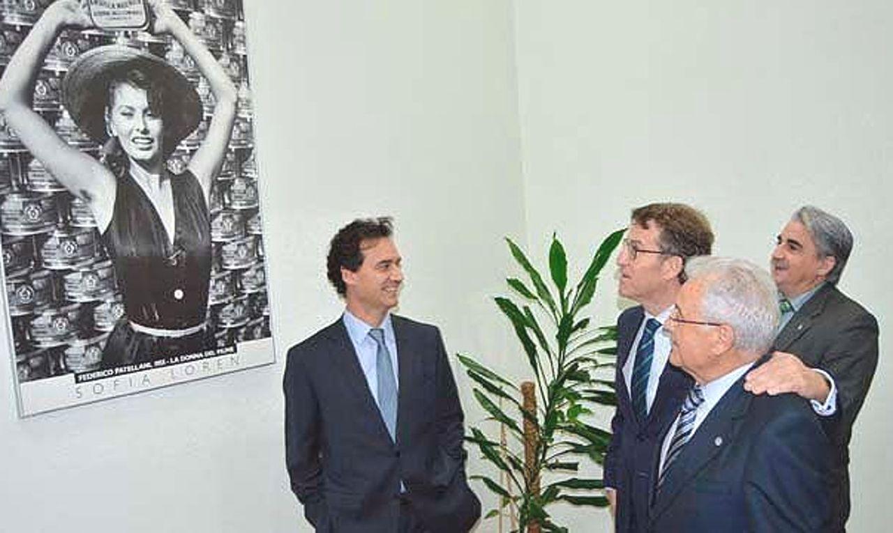 Jes�s Alonso Escur�s, izqda., muestra al presidente de la Xunta, Alberto N��ez Feij�o, acompa�ado de Jes�s Alonso y Juan Jos� Dieste, la foto que inspir� el logo de Rianxeira.  - FOTO: Jealsa