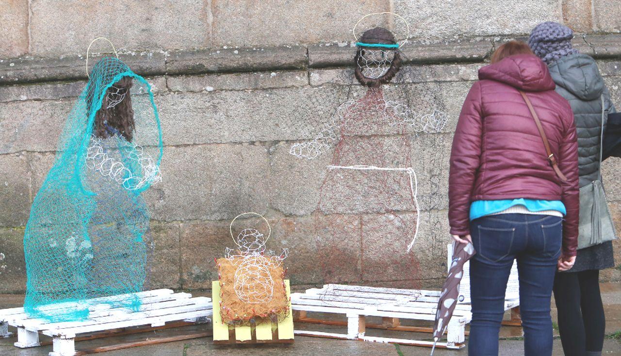 Arriba unos peatones contemplando el Belén del Obradoiro, pegado al Pazo de  Xelmírez, y abajo los detalles de la Virgen María y el niño Jesús. Fotos:  - FOTO: Fernando Blanco