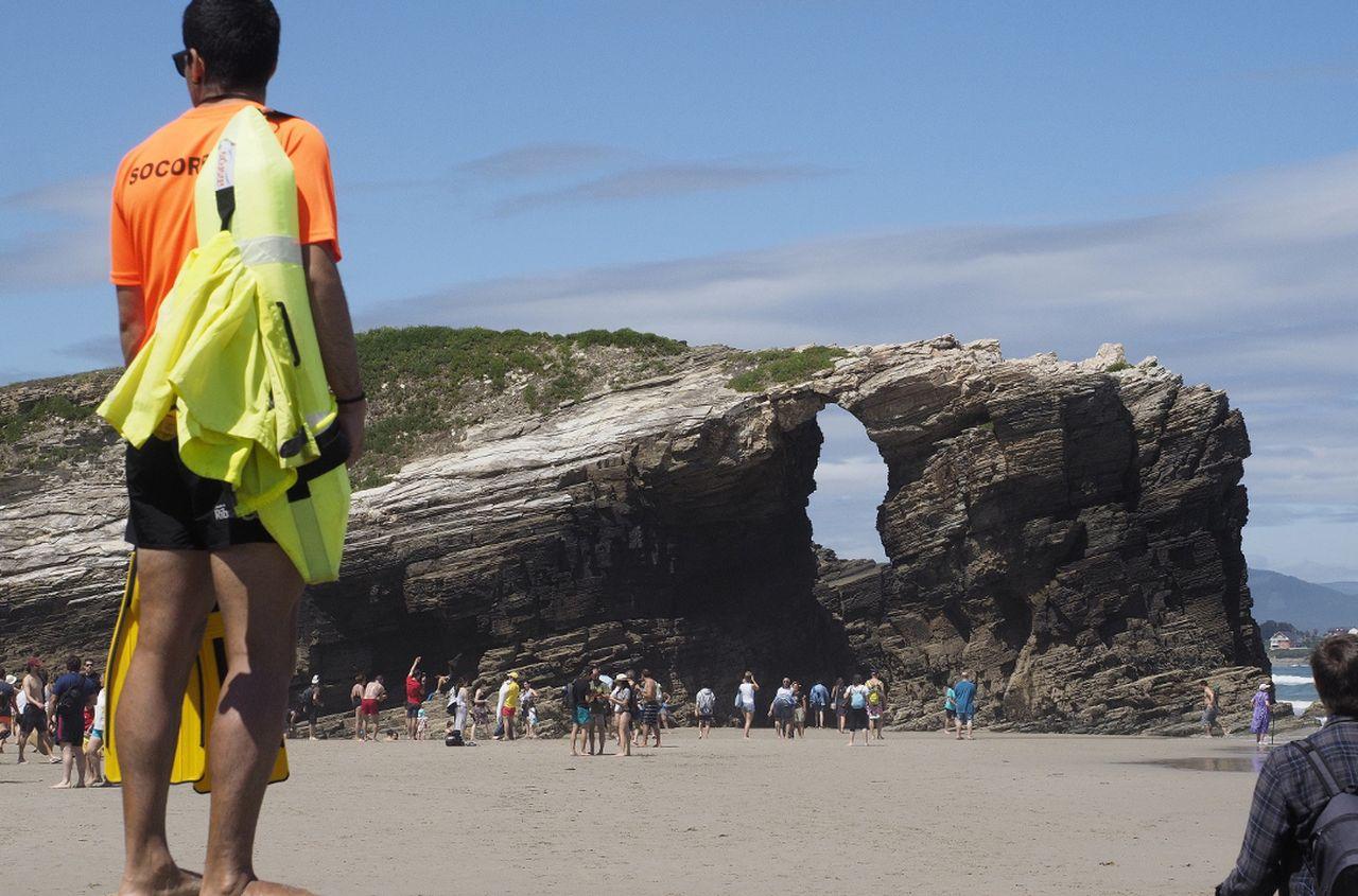 Un socorrista vigilando ayer la playa de las Catedrales, en Ribadeo, en un día con muchos visitantes.   - FOTO: Eliseo Trigo/Efe